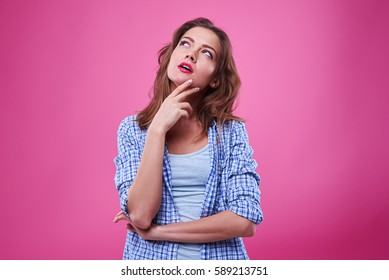 Studio shot of preoccupied girl looking upwards and making decision. Isolated over pink background