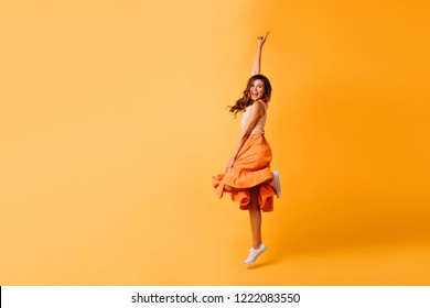 Studio shot of pretty girl in orange skirt and white shoes. Excited red-haired lady jumping on yellow background.