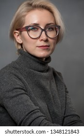 Studio shot of pretty serious middle aged woman in glasses with short hairstyle dressed casually looking at camera