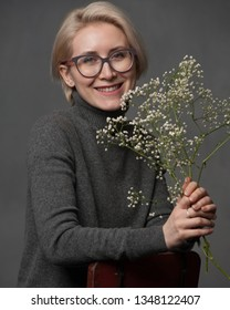 Studio shot of pretty smiling middle aged woman in glasses with short hairstyle dressed casually looking at camera