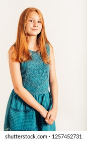 Studio shot of pretty teenage girl with red hair, wering blue dress, posing on white background