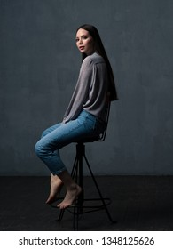 Studio shot of pretty young female with long beautiful hair dressed casually. Young confident woman sitting on chair and looking at camera