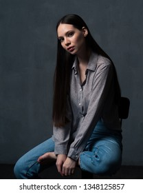 Studio shot of pretty young female with long beautiful hair dressed casually. Young barefoot woman sitting on chair and looking at camera