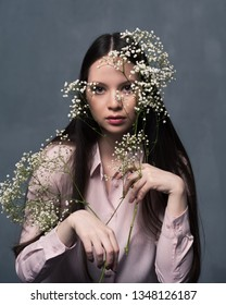 Studio shot of pretty young female with long beautiful hair dressed casually. Young confident woman with flower in her hand looking at camera
