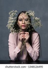 Studio shot of pretty young female with long beautiful hair dressed casually. Young woman looking at camera through flowers