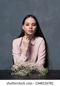 Studio shot of pretty young female with closed eyes and white flower gypsophila in her hand dreaming