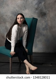 Studio shot of pretty young female with long beautiful hair dressed white sweater. Young barefoot woman sitting on green armchair and looking away