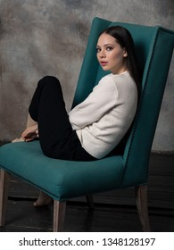 Studio shot of pretty young female with long beautiful hair dressed white sweater. Young barefoot woman sitting on green armchair and looking at camera