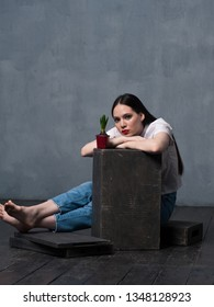 Studio shot of pretty young female with growing flower in pot. Young barefoot woman sitting on wooden floor and looking at camera