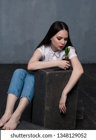 Studio shot of pretty young female with growing flower in pot. Young barefoot woman sitting on wooden floor and looking at plant