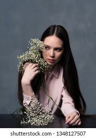Studio shot of pretty young woman with long beautiful hair and white flower gypsophila in her hand looking away