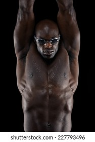 Studio shot of professional swimmer training over black background. Young african athlete with swimming goggles. Sports and fitness concept.