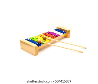 Studio shot a rainbow colored wooden xylophone with sticks over white background. Educational, musical development toy for kid and toddlers. Colorful metallophone toy for learn and enjoy tones,  sound
