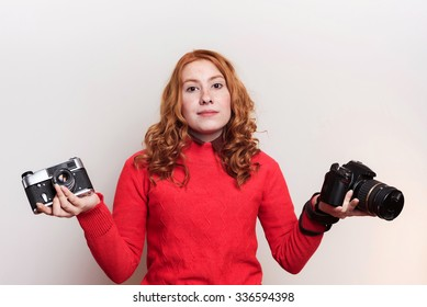 studio shot of redhead woman holding vintage camera and modern camera and making a choice. Old and modern concept