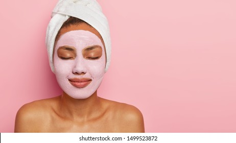 Studio shot of relaxed woman with healthy dark skin, applies mineral clay mask on face for rejuvenation, keeps eyes shut, has white towel on head, isolated on pink wall, blank space for your advert