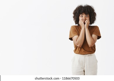 Studio shot of scared african american teenage girl in stupor popping eyes at camera and covering mouth not to scream with hands being terrifyied and frightened trembling from fear and shock