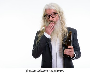 Studio shot of senior bearded businessman holding bottle of beer and looking shocked