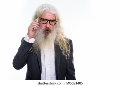 Studio shot of senior bearded businessman talking on mobile phone while looking tired