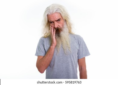 Studio shot of senior bearded man looking upset with hand on face