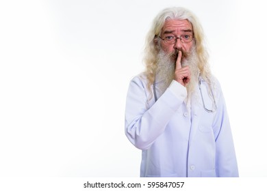 Studio shot of senior bearded man doctor with finger on lips