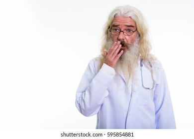 Studio shot of senior bearded man doctor looking shocked while covering mouth