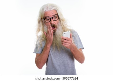 Studio shot of senior bearded man using mobile phone while looking shocked and covering mouth