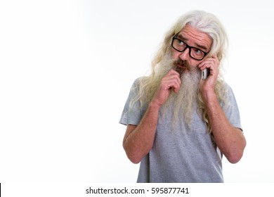 Studio shot of senior bearded man thinking and looking up while talking on mobile phone