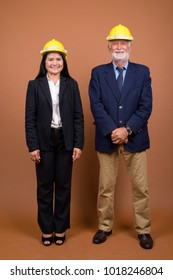 Studio shot of senior businessman and mature Asian businesswoman together against brown background