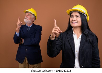 Studio shot of senior businessman and mature Asian businesswoman with hardhat together against brown background
