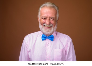 Studio shot of senior handsome man wearing stylish clothes against brown background