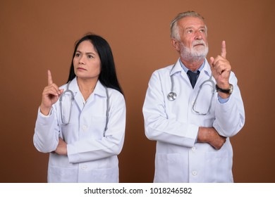 Studio shot of senior man doctor and mature Asian woman doctor together against brown background