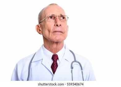 Studio shot of senior man doctor thinking isolated against white background