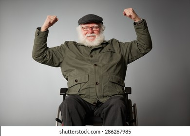 Studio shot of senior man sitting in wheel chair cheering with his fist clenched against grey background