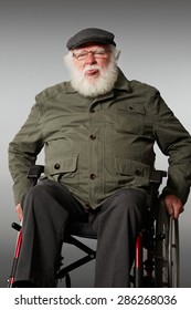 Studio shot of senior man sitting on wheel chair teasing, sticking out his tongue against grey background