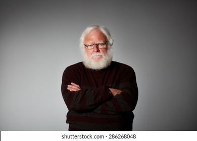 Studio shot of senior man standing with his arms crossed looking upset against grey background