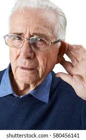 Studio Shot Of  Senior Man Suffering From Deafness