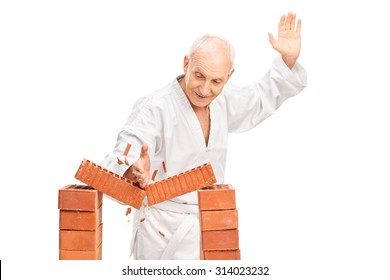 Studio shot of a senior man in a white kimono breaking a brick with his bare hand isolated on white background