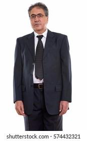 Studio shot of senior Persian businessman standing while wearing eyeglasses