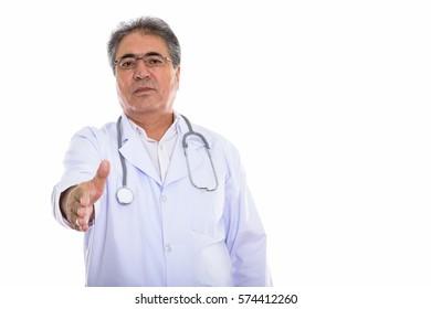 Studio shot of senior Persian man doctor giving handshake
