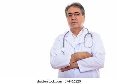 Studio shot of senior Persian man doctor with arms crossed