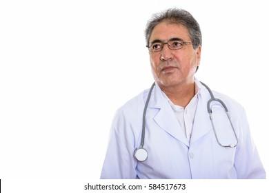 Studio shot of senior Persian man doctor thinking while looking at distance
