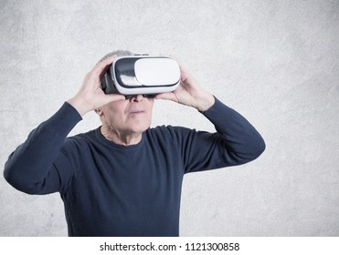 Studio shot of a senior using a VR headset on gray background