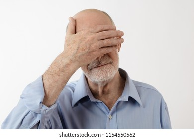 Studio shot of senior white bearded man in blue shirt hiding face behind palm, feeling ashamed, shy or embarrassed. Elderly Caucasian male with bald head covering eyes with hand. Body language