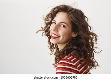 Studio shot of sensual good-looking female with curly hair standing on windy weather half-turned and smiling while wearing red lipstick, hair is waving in air. Model makes photoshoot for her portfolio
