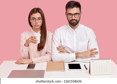Studio shot of serious female and female perfectionist, being well organized, wear spectacles, everything on right place at working place, drink coffee, work together on new project, isolated on pink