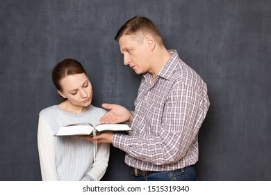 Studio shot of serious man holding book, pointing with hand at text and explaining something to focused woman looking attentively at book and trying to understand information, over gray background