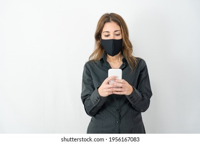 Studio shot of serious young model woman in business shirt clothes isolated on white copy space background looking at smartphone wearing medical protection mask. Stress for Covid-19 data news concept