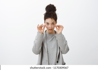 Studio shot of shocked disbelieving attractive european girl with curly hair combed in bun, taking off glasses, looking from under forehead focused and intrigued, standing amazed over gray wall