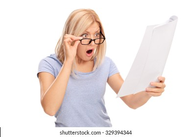 Studio shot of a shocked woman looking at the bills in disbelief isolated on white background
