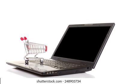 Studio shot of a  shopping cart over a laptop computer